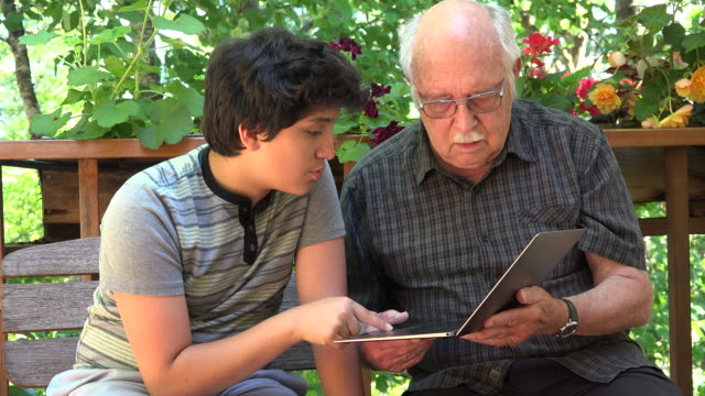 stockvideo's en b-roll-footage met boy explains computer to grandfather - oudere internetgebruiker