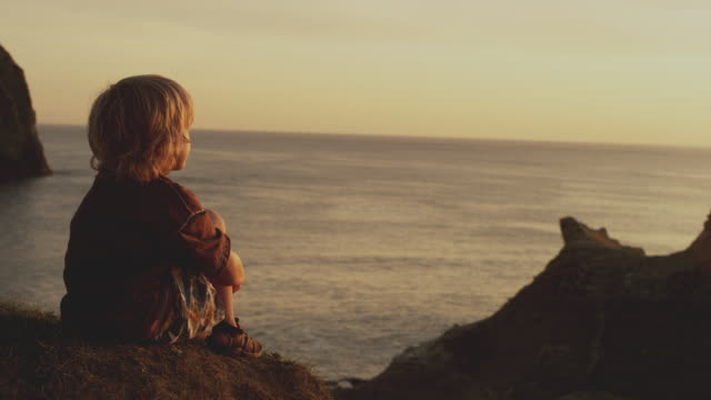 boy explores beach hill at sunset - guardare in una direzione video stock e b–roll