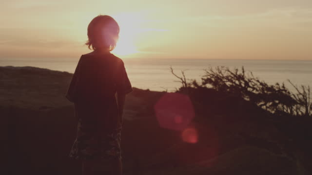 Boy explores beach hill at sunset