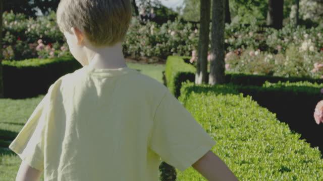 vídeos de stock, filmes e b-roll de boy explores garden with friend - brincadeira de pegar