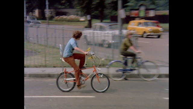 vidéos et rushes de montage boy failing to follow safety rules during bicycle competition / united kingdom - 1971