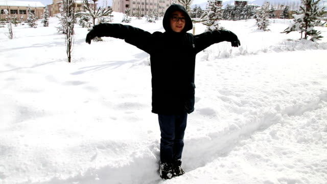 boy falling backwards onto the snow. fun in the snow. winter fun - back to front stock videos & royalty-free footage