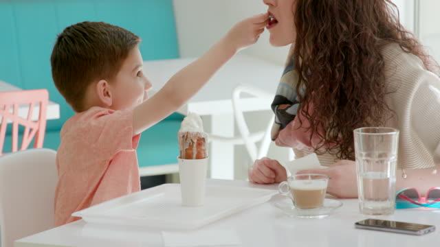 junge mutter mit soft serve ice cream mit löffel am tisch füttern - kegel stock-videos und b-roll-filmmaterial