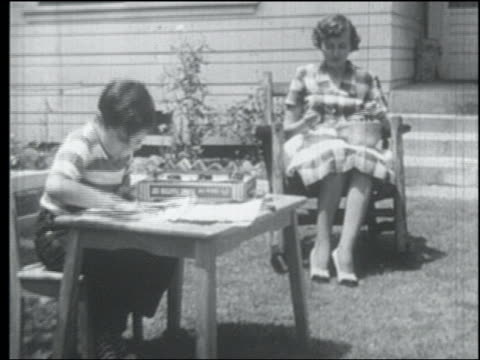 b/w 1952 boy finger painting as mother sits knitting outdoors - 1952 stock videos & royalty-free footage