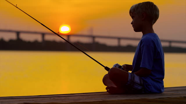 boy fishing at dawn or dusk - fishing rod stock videos & royalty-free footage
