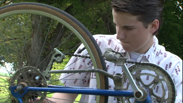 a boy fixes the chain on his bicycle. - repairing stock videos & royalty-free footage