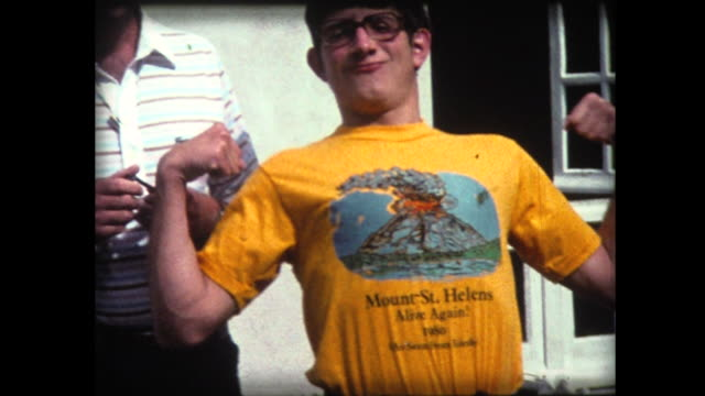 1980 boy flexes muscles in mt. st. helens tee shirt - maglietta video stock e b–roll