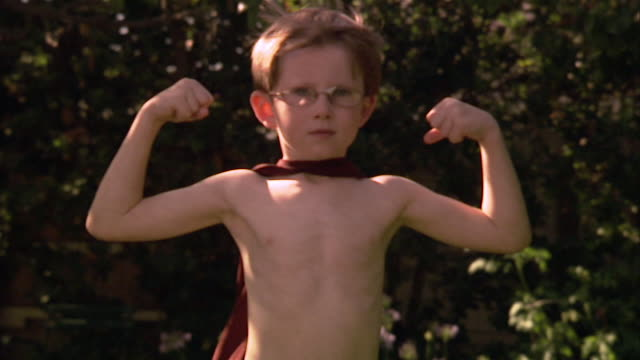 SLO MO MS Boy flexing muscles and wearing eyeglasses and superhero cape / Los Angeles, California, USA