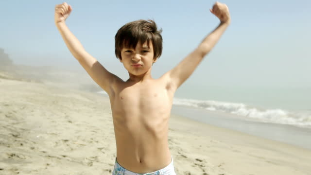 boy flexing muscles on beach - flexing muscles stock videos & royalty-free footage