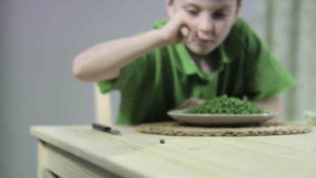 Boy flicking a pea off table