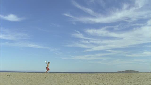 LA WS Boy flying kite and running across beach / Phippsburg, Maine, USA