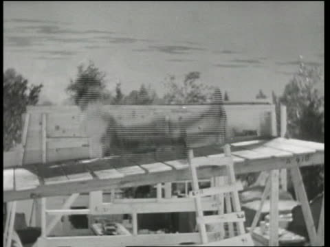 b/w 1935 boy flying up into air at construction site / why pay rent? - 1935 stock videos & royalty-free footage