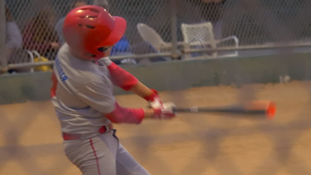 a boy gets a base hit batting and playing little league baseball game. - slow motion - hitting点の映像素材/bロール