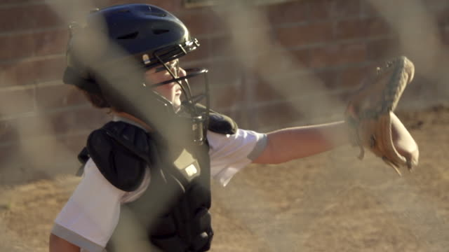 A boy gets hit in the face mask by the ball while playing catcher in a little league baseball game. - Slow Motion