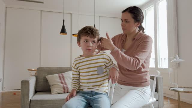 vídeos y material grabado en eventos de stock de niño que se corta el pelo durante la cuarentena para covid-19 - peinado