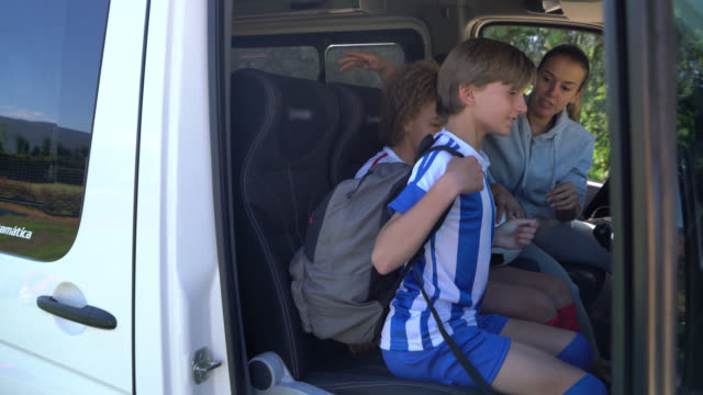 boy getting in the van ready for football practice and soccer mon hurrying him - urgency stock videos & royalty-free footage