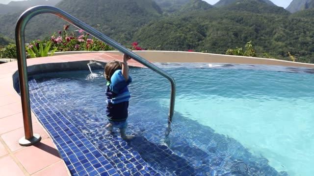 boy getting into pool - schwimmflügel stock-videos und b-roll-filmmaterial