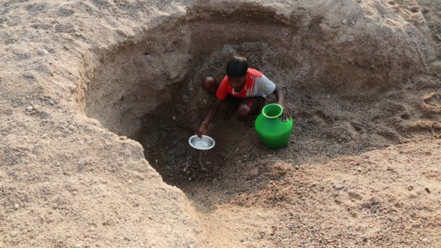 vídeos y material grabado en eventos de stock de boy getting water out of an almost empty waterhole near pannur, india - sediento