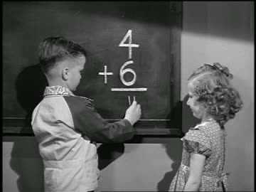 b/w 1949 boy + girl at chalkboard doing addition problem / girl corrects boy's mistake / industrial - skolbyggnad bildbanksvideor och videomaterial från bakom kulisserna