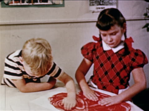 1950 boy + girl finger painting with red paint on table / educational - painting stock videos & royalty-free footage