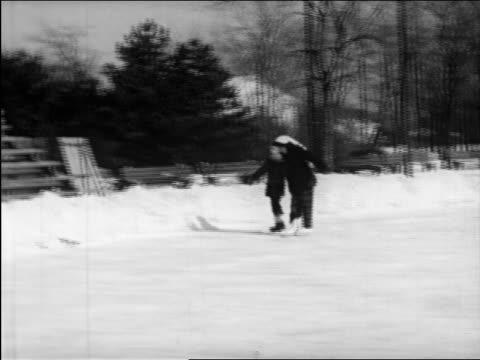 b/w 1948 pan boy + girl holding hands + ice skating on pond / instructional - ice skating stock videos & royalty-free footage
