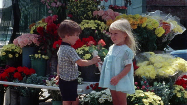 A boy gives a girl flowers then kisses her on the cheek in front of a flower stand.