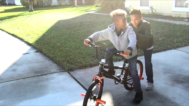 boy gives brother lift on his bicycle - family with two children stock videos & royalty-free footage