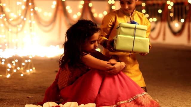 ms boy giving gifts to his sister and embracing in diwali festival - altruismo video stock e b–roll