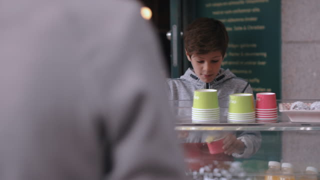 boy giving ice cream cup to female customer at stand in city - stockholm stock-videos und b-roll-filmmaterial
