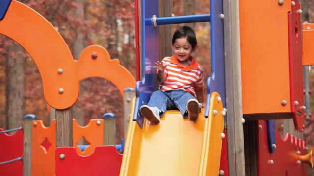vídeos de stock, filmes e b-roll de ms td boy (2-3) going down on playground slide into fathers arms / richmond, virginia, usa - deslizar