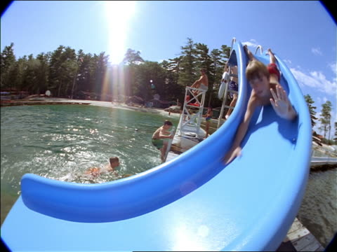 fisheye boy going down slide on stomach into lake surrounded by pine trees / other children in background - cinematography stock videos & royalty-free footage