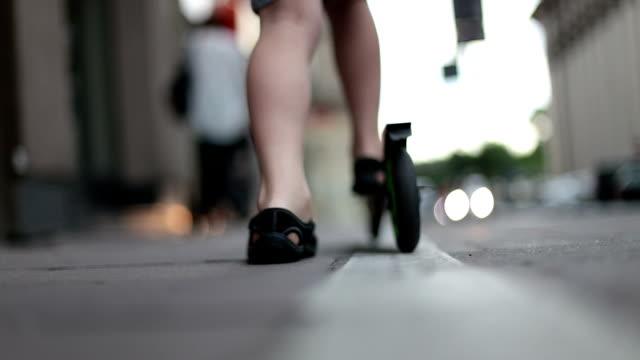 Junge geht auf dem Rollstuhl auf dem Gehweg im der Stadt