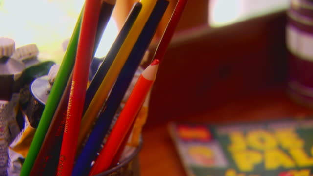 Boy grabbing colored pencils from jar, extreme close up