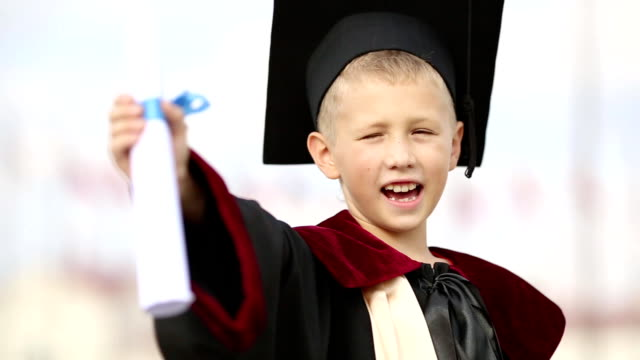 boy graduate with a diploma - graduation gown stock videos and b-roll footage