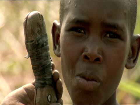 cu boy grasping machete handle in sugar cane field / kigali, rwanda - フツ族点の映像素材/bロール