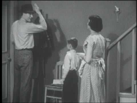 b/w 1950 boy greeting father at front door / mother enters + father gives them both money - hausfrau stock-videos und b-roll-filmmaterial