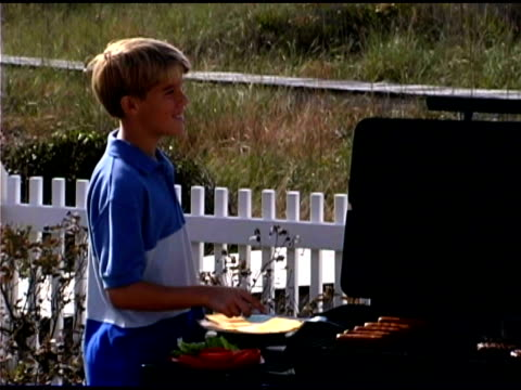 boy grilling and waving to family - see other clips from this shoot 1335 stock videos and b-roll footage
