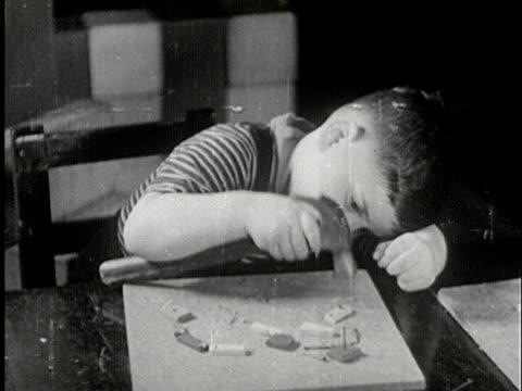 ms, b/w, boy hammering nail into piece of wood sitting at desk, usa - hammer stock-videos und b-roll-filmmaterial