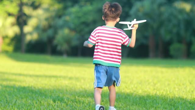 junge hand hält ein papierflugzeug - segelflugzeug stock-videos und b-roll-filmmaterial