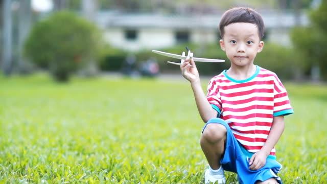 vídeos y material grabado en eventos de stock de mano de niño sosteniendo un avión de papel - avión de papel