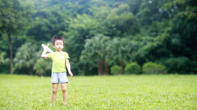 vídeos y material grabado en eventos de stock de mano de niño sosteniendo un avión de papel, hd slow motion - avión de papel