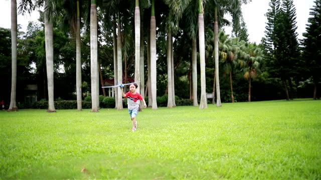 junge hand hält einen papierflieger, hd slow motion - segelflugzeug stock-videos und b-roll-filmmaterial
