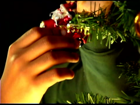 boy hanging ornament on christmas tree - see other clips from this shoot 1407 stock videos and b-roll footage