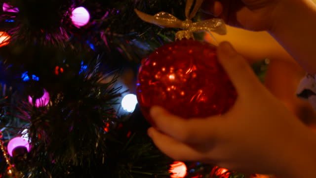boy hangs a ball on the christmas tree in the new year - spruce stock videos & royalty-free footage