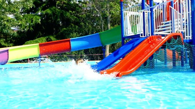 pojken har kul på vattenrutschbana i hotellets pool - utebassäng bildbanksvideor och videomaterial från bakom kulisserna