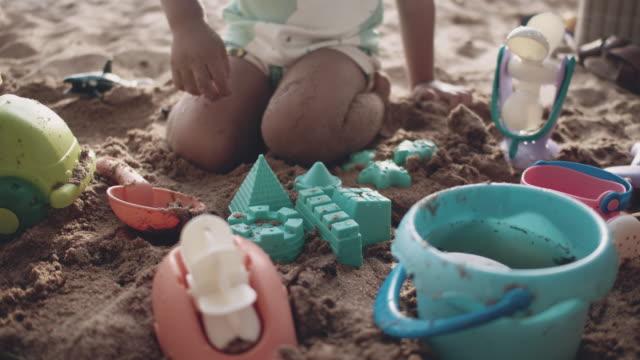 vidéos et rushes de un garçon ayant l'amusement avec le château de sable sur la plage - un seul bébé garçon