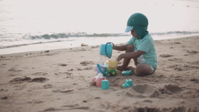 a boy having fun with sand castle on beach - one baby boy only stock videos & royalty-free footage