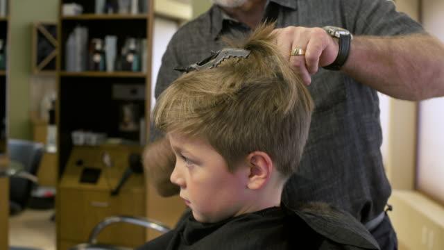 boy having his hair cut in a barbershop - cutting hair stock videos and b-roll footage