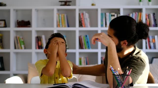 pojke har problem med att avsluta läxor - enbarnsfamilj bildbanksvideor och videomaterial från bakom kulisserna