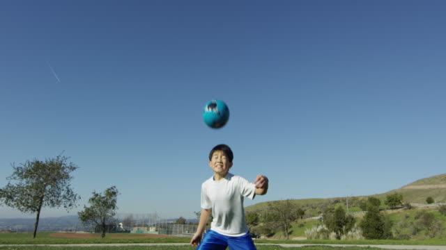 boy heading soccer ball - geköpft stock-videos und b-roll-filmmaterial